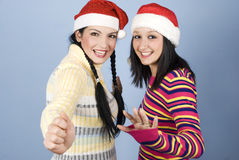 Two laughing girls with Santa hat. Two laughing happy beautiful girls wearing Santa hat and having fun on blue background,check also  Christmas time,santa women Stock Photography