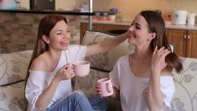 Two sisters drink coffee sitting on the couch. Two laughing girls in sexy white t-shirts and ripped jeans sit on the couch, drink coffee and laugh. Family stock footage