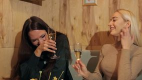 Two laughing girls sitting in cafe with champagne. Two young girls laughing and sitting in a cafe with champagne stock video