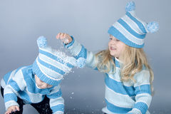 Two laughing girls in snow. Two cute girls laughing and playing in snow (studio Royalty Free Stock Photos