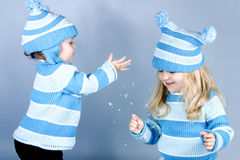 Two laughing girls in snow. Two cute girls laughing and playing in snow (studio Stock Image