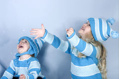 Two laughing girls in snow. Two cute girls laughing and playing in snow (studio Stock Photography