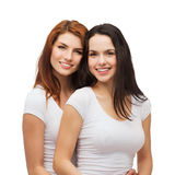 Two laughing girls in white t-shirts hugging Stock Photography