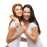 Two laughing girls in white t-shirts hugging Stock Image
