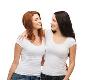 Two laughing girls in white t-shirts hugging Royalty Free Stock Photos