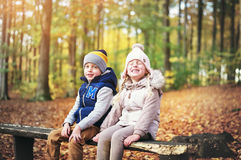 Two laughing kids sitting on a bench Royalty Free Stock Photo