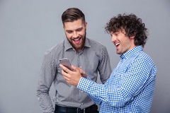 Two laughing men using smartphone Stock Photo