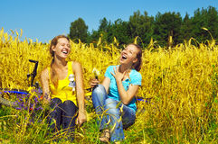 Two laughing pretty girls rest in golden field. Two laughing pretty girls rest in the golden field Royalty Free Stock Photo