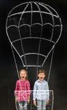 Two laughing schoolchildren flying on imaginary drawn air baloon. Two laughing little schoolchildren flying on imaginary drawn air baloon on the blackboard Royalty Free Stock Photos