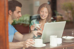 Two laughing students working at laptop royalty free stock images