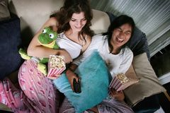Two laughing teenage girls. A view of two teenage girls in pajamas, eating popcorn and laughing while watching a move. One girl is American Indian and the other Stock Image