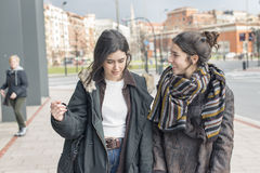 Two laughing woman friend talking. Two women friends walking and talking in the street Royalty Free Stock Photography