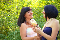 Two laughing women with dandelions in a summer park Stock Photos