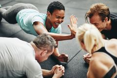 Two laughing women high fiving while planking at the gym. Two fit young women in sportswear laughing and high fiving together while planking with a couple of stock photos