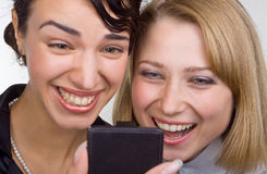Two laughing women look at mobile phone Royalty Free Stock Photo