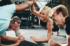 Female friends high fiving while planking at the gym. Two laughing young women in sportswear high fiving together while planking with a couple of male friends royalty free stock photos