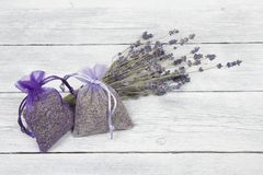 Lavender sachets and a bunch of dried lavender flowers on a white wooden planks background Stock Photography