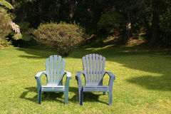 Two Lawn Chairs. In an outdoors garden area Stock Image