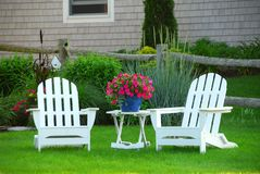 Two lawn chairs. In a beautifl garden near cottage Royalty Free Stock Image