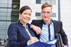 Two lawyers with files smiling. Two happy lawyers with files smiling in front of their office Royalty Free Stock Photo