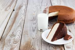 Chocolate-cottage cheese cake and milk on wooden background. Stock Photos