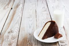 Chocolate-cottage cheese cake and milk on wooden background. Stock Image