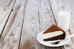 Chocolate-cottage cheese cake and milk on wooden background. Royalty Free Stock Photo