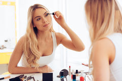 Two layers of mascara. Beautiful young woman applying mascara and looking at her reflection in mirror while sitting at the dressing table Stock Photo