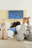 Two Laying Down on Floor Watching TV Stock Image