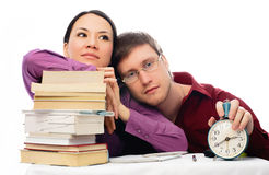 Two lazy students. Sitting by the table with a lot of books and unwilling to do homework Royalty Free Stock Photo