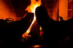 Boots by fire. Two leather boots in front of a fireplace stock images