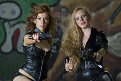 Two leather clad gun girls stock image