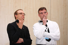 Two lecturers stand at a thoughtful pose Royalty Free Stock Photo