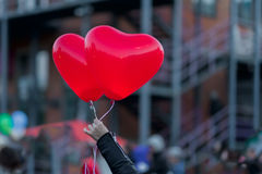 Two LED balloons in the form of scarlet burning hearts in the evening in girl`s hand. For a romantic background, for Royalty Free Stock Photography