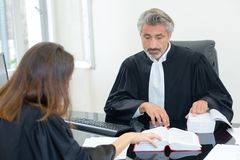 Two legal workers referring to reference book. Legal stock photography