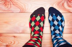 Two legs in different motley socks on a wooden floor royalty free stock photo