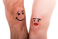 Two legs with faces, white background Stock Photo