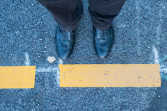 Two legs with shoes and yellow line Royalty Free Stock Photos