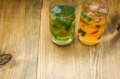Two lemonade with ice. Two glasses of lemonade with leaves of mint and cubes of ice on a wooden background Stock Images