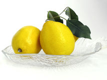 Two lemons. On crystal plate Royalty Free Stock Photos