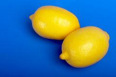 Two lemons. On a dark blue background Royalty Free Stock Images