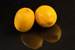 Two lemons on a black background. Fresh two lemons on a black background Royalty Free Stock Images
