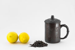 Two lemons, chinese mug and dry tea  on white background Royalty Free Stock Images