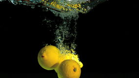 Two lemons dropping into water. In slow motion stock footage