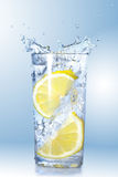 Two lemons fell in a glass. With water on gradient background Stock Photo