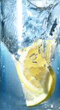 Two lemons fell in water. Two lemons fell in a glass with water on gradien background Royalty Free Stock Photos