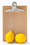Two lemons in front of the bulletin wooden table Royalty Free Stock Image