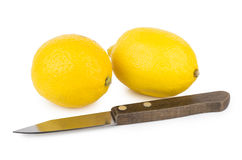 Two lemons and kitchen knife with wooden handle Royalty Free Stock Photo