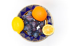 Two lemons, orange and plums on a plate Royalty Free Stock Photography