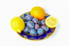 Two lemons, orange and plums on a plate Royalty Free Stock Image